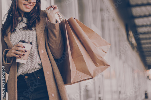 Beautiful fashionable woman drink coffee walking near mall with shopping bags. - 300463049