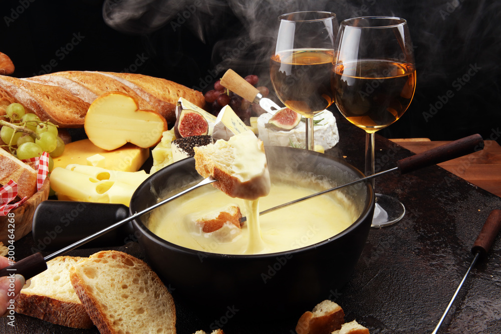 Fototapety, obrazy: Gourmet Swiss fondue dinner on a winter evening with assorted cheeses on a board alongside a heated pot of cheese fondue with two forks dipping