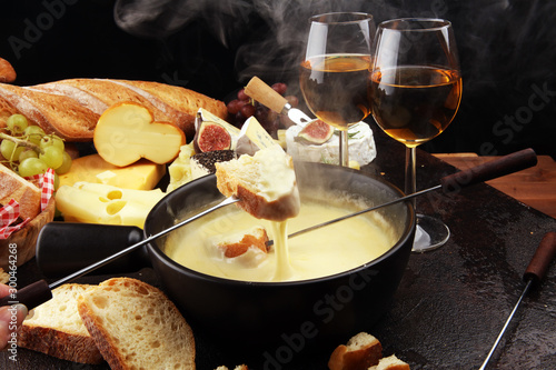 Gourmet Swiss fondue dinner on a winter evening with assorted cheeses on a board alongside a heated pot of cheese fondue with two forks dipping - 300464268