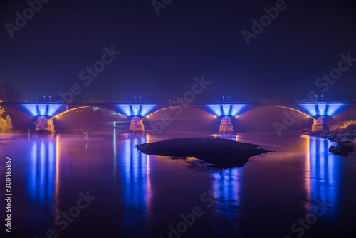 Concrete bridge with beautiful blue lights reflected in the lake at night in Pavia, Italy