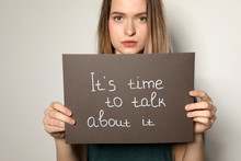Young Woman Holding Card With Words IT'S TIME TO TALK ABOUT IT Against Light Background