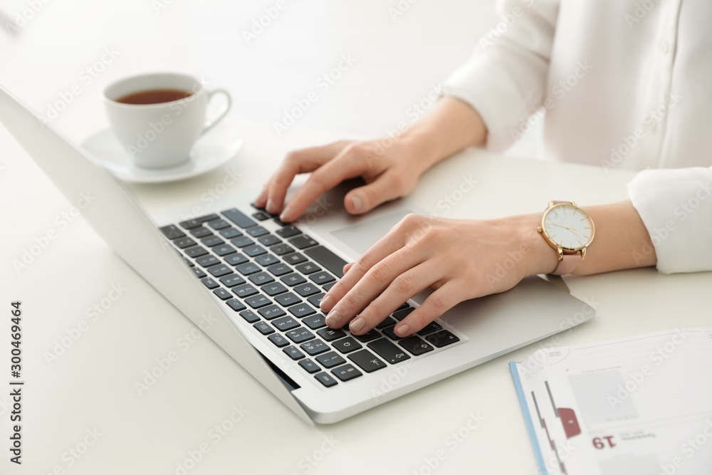 Fototapeta Young businesswoman using laptop at table in office, closeup