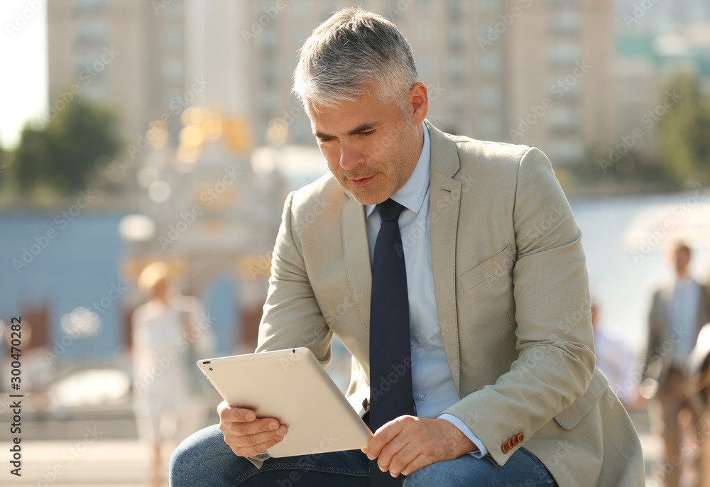 Fototapeta Portrait of handsome businessman with tablet in city