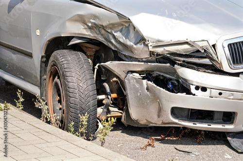 Fotografie, Tablou  Closeup detail of crashed car front headlight and deformed bumper, wheel tire an