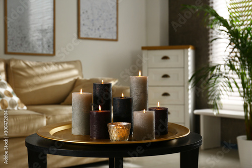 Canvastavla Tray with different burning candles on table in room