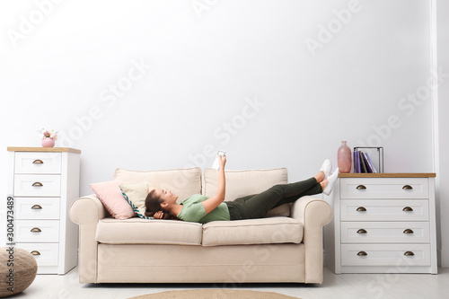 Fotografia  Happy young woman switching on air conditioner with remote control at home