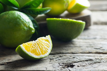 Fresh Ripe Organic Whole And Sliced Green Lemons On Wooden Rustic Background, Lime Citrus Healthy Fruit Concept