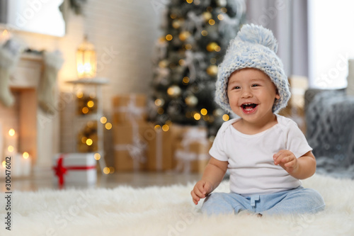 Obraz Little baby wearing knitted hat on floor at home. First Christmas - fototapety do salonu
