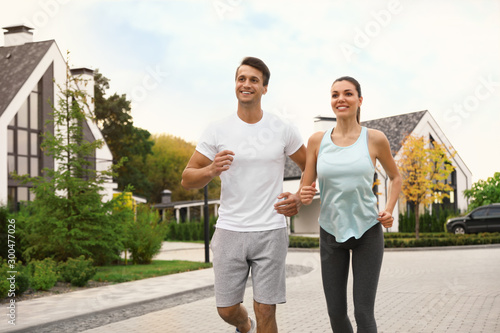 Fotografie, Obraz  Sporty couple running on street. Healthy lifestyle