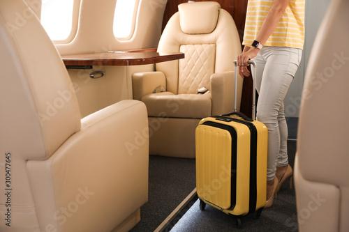 Obraz na plátně Woman with modern color suitcase on plane