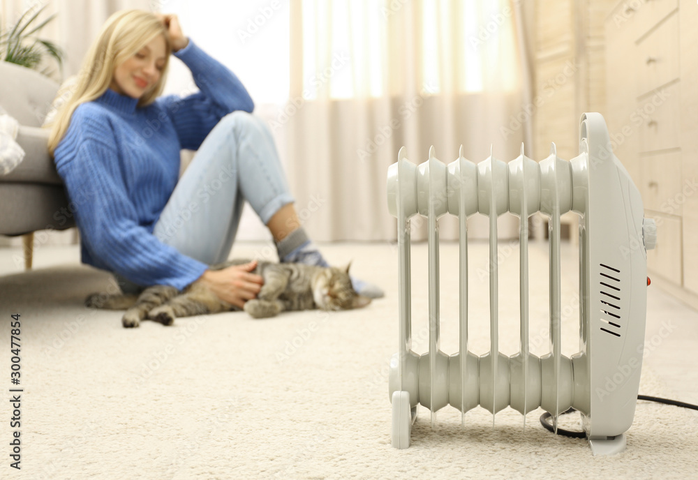 Fototapety, obrazy: Electric heater and blurred young woman with cute tabby cat on background. Space for text