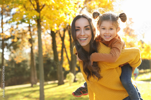 Happy woman with little daughter in sunny park. Autumn walk - 300478066