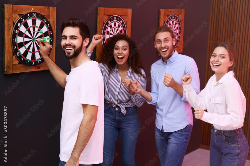 Fototapeta Group of friends playing darts in bar