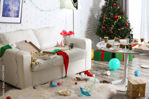 Photo Messy living room interior with Christmas tree. Chaos after party