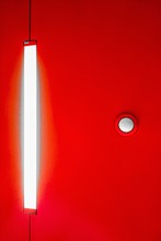 Vertical Shot Of A Red Wall With A Bright Rectangular White Light Bulb