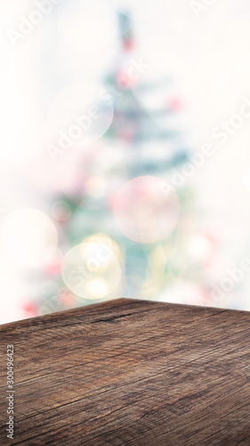 Fotografie, Obraz  Empty angle brown wood table with abstract Christmas tree decor string light blur background,Holiday backdrop,Mockup vertical banner for display of product and advertise on online media