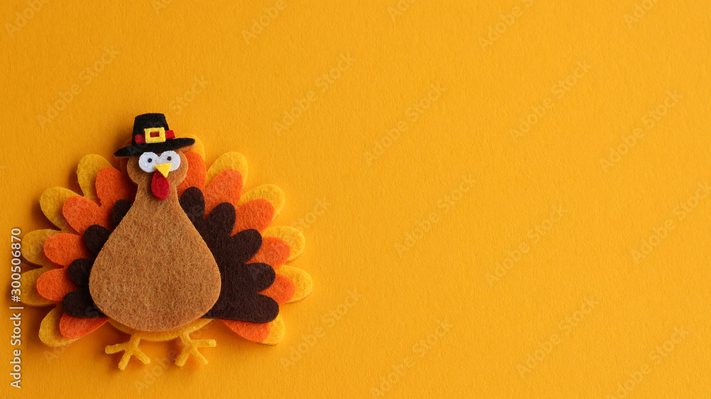 Fototapeta orange brown and yellow crafted felt turkey laying flat on an orange background with copy space