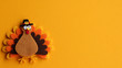 orange brown and yellow crafted felt turkey laying flat on an orange background with copy space