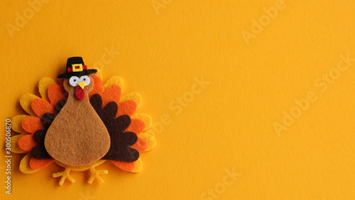 orange brown and yellow crafted felt turkey laying flat on an orange background Canvas Print