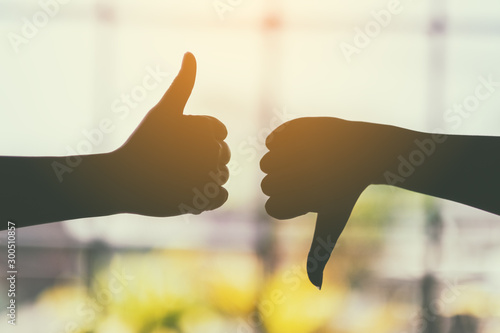 Fotomural  Silhouette image of two hands making thumbs up and thumbs down sign