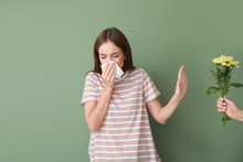 Young Woman With Allergy Refusing To Take Bouquet On Color Background