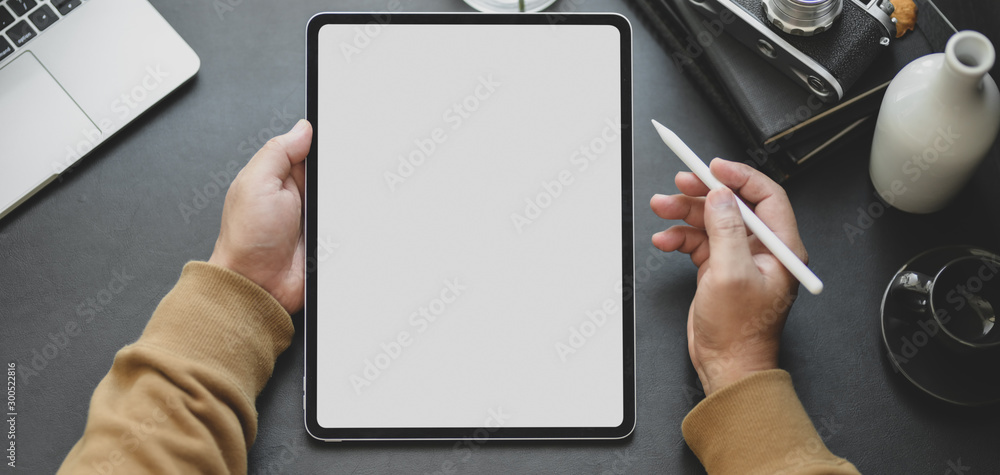 Fototapeta Close-up view of man using blank screen tablet while working in dark modern workplace