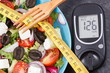 Glucose meter with sugar level, centimeter and greek salad. Diabetes, slimming, healthy lifestyles and nutrition