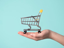 Toy Shopping Cart In Female Hand.Shopping Trolley On Hand Over Blue Background.Copy Space For Text Or Design.Shop Trolley Seamless Pattern As Sale,discount,shopaholism Concept.Consumer Society Trend