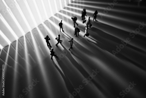 Fotomural  Miniature toys studio set up - Top view of black and white effect of people with long shadows busy walking during sunrise or sunset