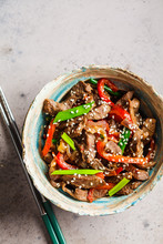 Asian Teriyaki Beef With Green Onions And Sesame Seeds In Beautiful Bowl, Gray Background, Top View.