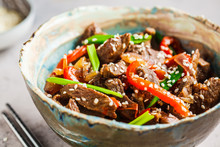 Asian Teriyaki Beef With Green Onions And Sesame Seeds In Beautiful Bowl, Gray Background.