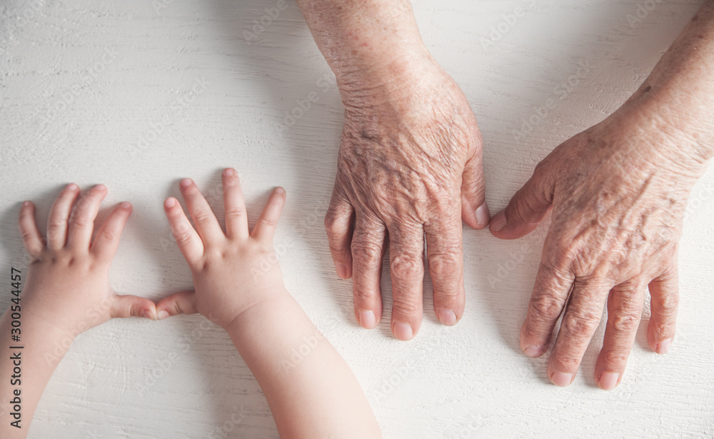 Fototapety, obrazy: Elderly woman and a kid hands together.