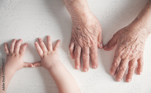 Fotomural  Elderly woman and a kid hands together.