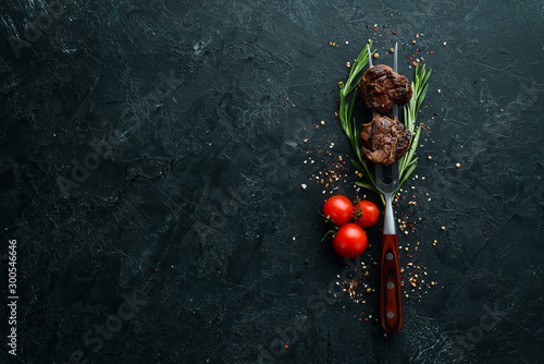 Obraz Baked veal on a fork. Veal steak on black stone background. Top view. Free space for your text. - fototapety do salonu
