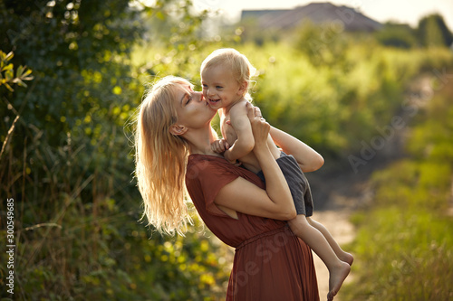 Pretty young mother kissing her beloved son - country background