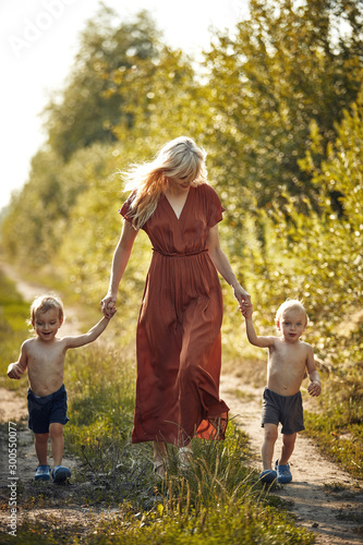Poster Artist KB Cheerful mother walking with her two adorable twin-sons