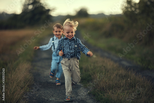 Poster Artiste KB Two adorable boys running on the country road