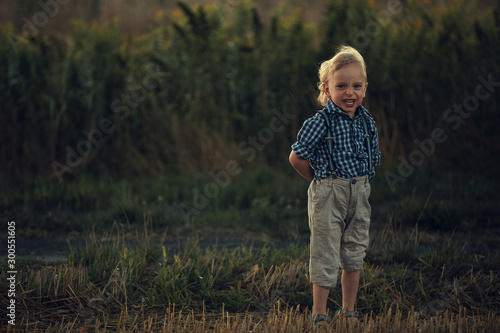 Portrait of a little blond boy in the countryside