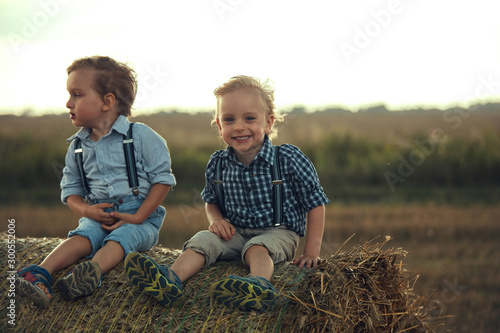 Photo sur Toile Artiste KB Portrait of cheerful children sitting on a sheaf