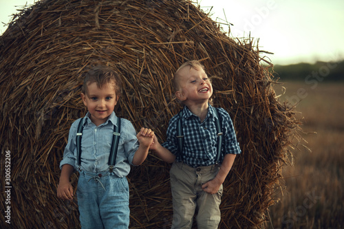 Staande foto Artist KB Two cute brothers leaning on the sheaf