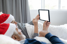 Elderly Couple Caucasian Senior Man And Woman With Red Hat Using Internet On Tablet With White Screen Background For Christmas Festival Day In Bedroom, Retirement Love Family Lifestyle Concept
