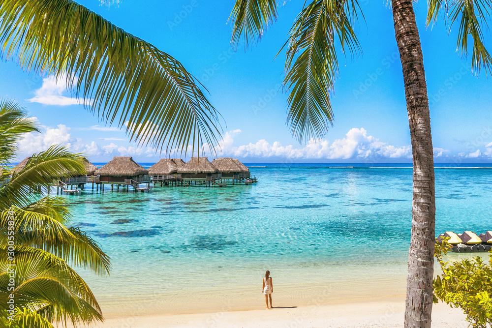Fototapeta Luxury Tahiti beach resort travel tourist walking on Polynesian beach ocean water at overwater bungalow hotel in French Polynesia, Moorea island in south pacific, famous getaway destination.