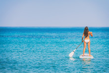 Paddle Board Bikini Woman Standing Paddling Away On Stand Up Paddleboarding On Ocean Blue Background Water. Hero View Of Girl Standing On Sup Surfboard Watersport Leisure Activity.