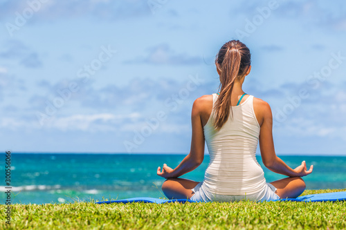 Yoga meditation woman meditating in lotus pose on exercise mat on beach grass.