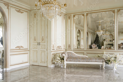 Fototapeta Christmas morning. Classic luxurious apartments with decorated christmas tree and presents. Living with fireplace, columns and stucco. obraz