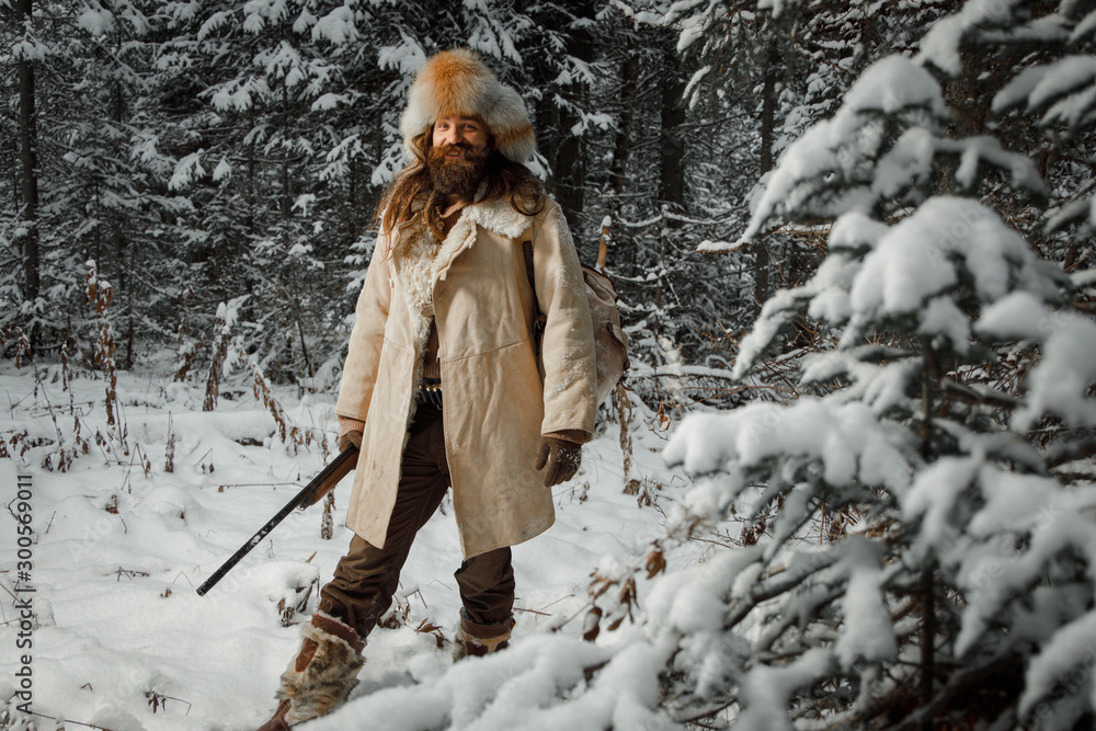Fototapety, obrazy: Hunter in vintage winter clothes with gun sneaks through forest