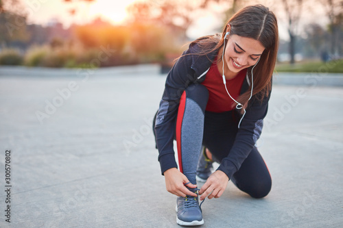 Fotomural  Young modern woman tying running shoes in urban park.