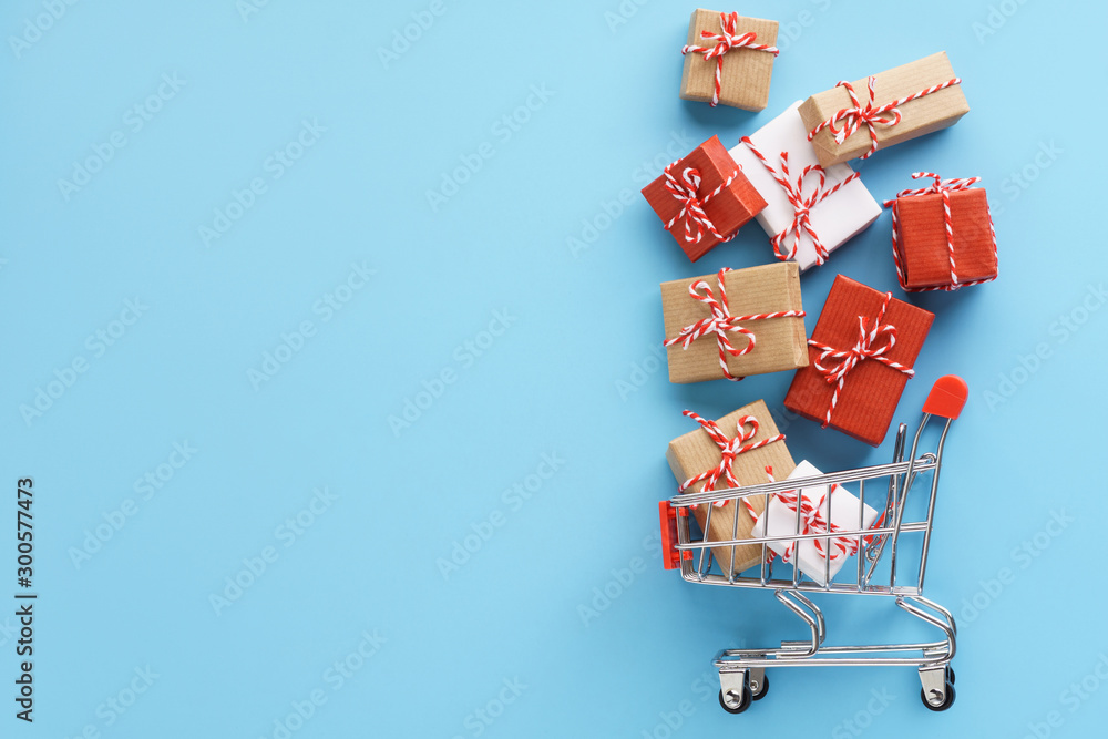 Fototapeta Gift boxes flying out of a shopping cart on black background.