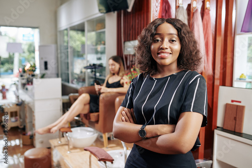 Photo Portrait of pretty young manicurist smiling at camera, her client waiting for pe
