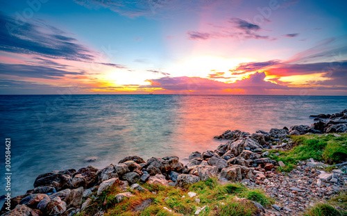 Fototapeten See sonnenuntergang Rocks on stone beach at sunset. Beautiful landscape of calm sea. Tropical sea at dusk. Dramatic colorful sunset sky and cloud. Beauty in nature. Tranquil and peaceful concept. Clean beach in Thailand.